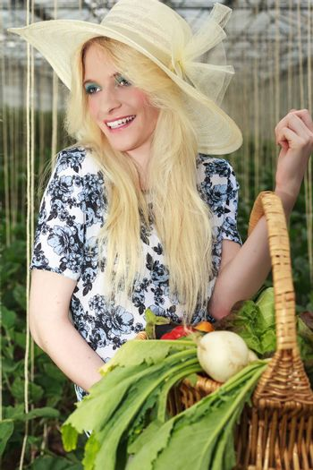 Close up Happy Blond Woman Wearing Fashionable Off-White Straw Hat, Carrying Basket of Fresh Vegetables in the Farm and Looking Into the Distance.