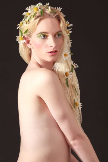 Half Body Shot of a Naked Pretty Young Woman with Flowers on her Long Blond Hair, Looking Into the Distance Against Black Background.