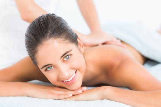 Pretty brunette enjoying a massage smiling at camera