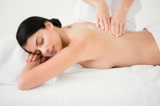 Woman receiving a salt scrub massage