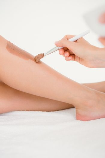 Therapist waxing womans leg at spa center