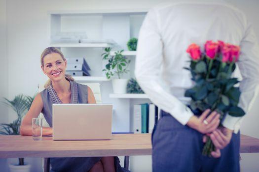 Man hiding bouquet in front of businesswoman at desk