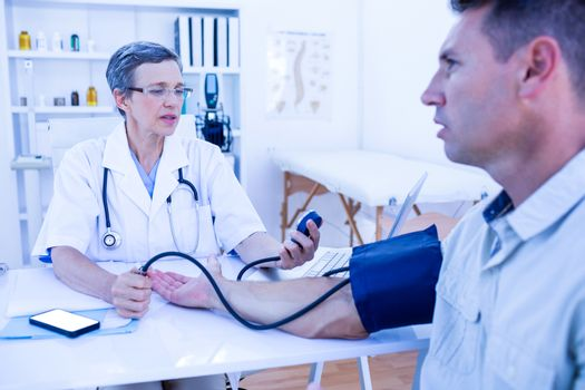 Doctor checking blood pressure of her patient