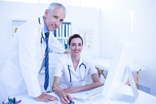 Portrait of smiling medical colleagues working with computer and looking at camera