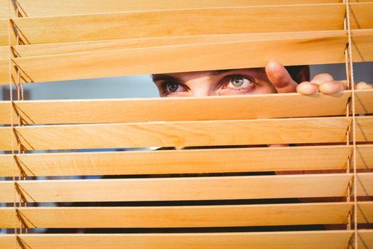 Hipster businessman peeking through blinds