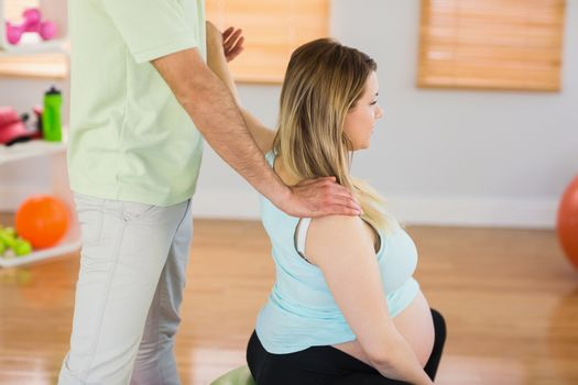Pregnant woman having relaxing massage while sitting on exercise ball