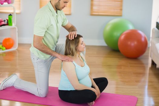 Pregnant woman getting massage for neck and shoulders