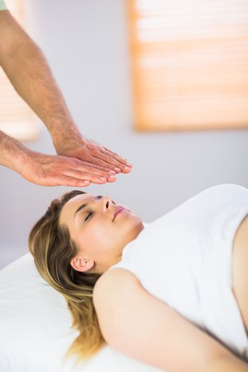 Close up view of pregnant woman getting reiki treatment