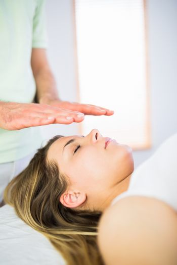 Close up view of relaxed pregnant woman getting reiki treatment