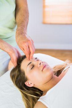 Relaxed pregnant woman enjoying head massage