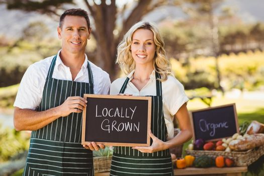 Smiling farmer couple holding locally grown sign
