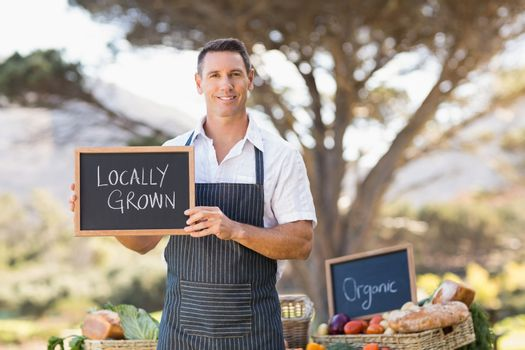 Smiling farmer holding a locally grown sign