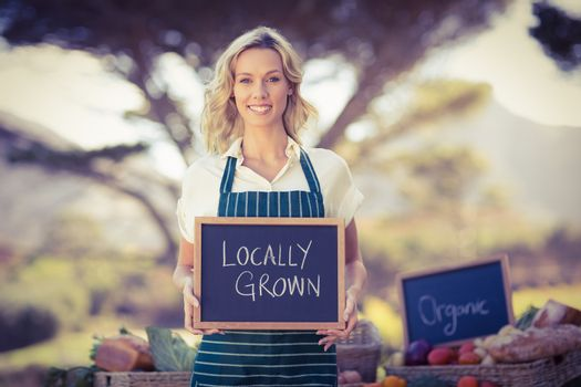 Smiling farmer woman holding a locally grown sign