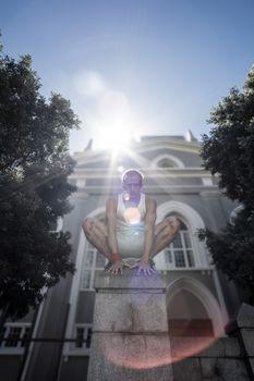 Extreme athlete crouching on pillar