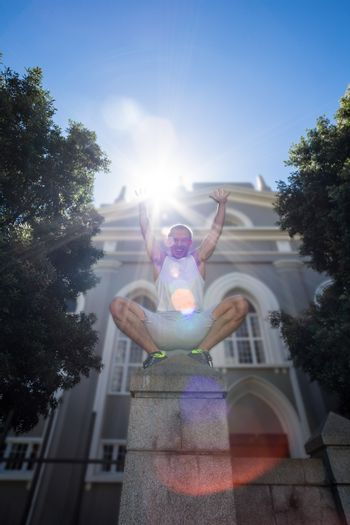 Extreme athlete crouching on pillar and holding arms up in the air