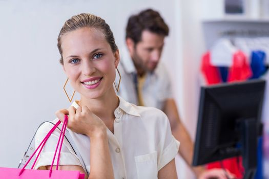 Smiling woman standing in front of till
