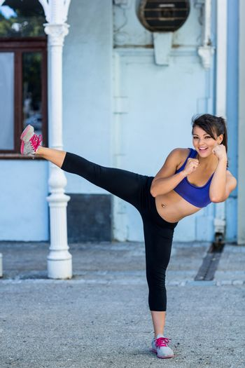Portrait of smiling athletic woman doing martial arts