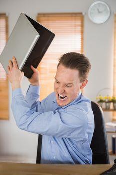 Furious businessman about to smash his laptop