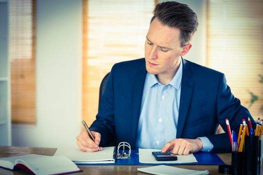 Concentrated businessman writing down