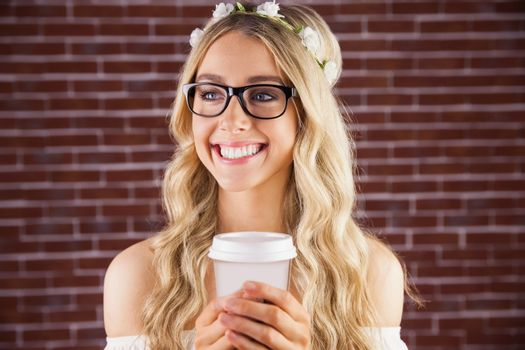 Gorgeous smiling blonde hipster with floral headband and coffee