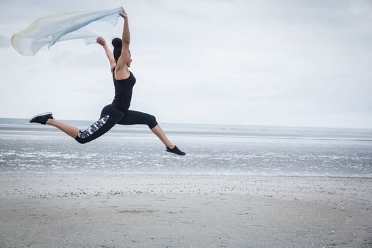 Fit girl leaping with scarf