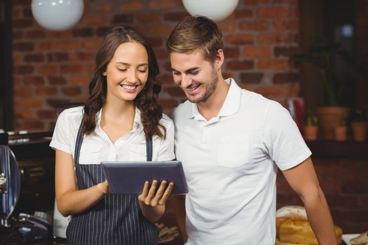 Smiling co-workers using a tablet