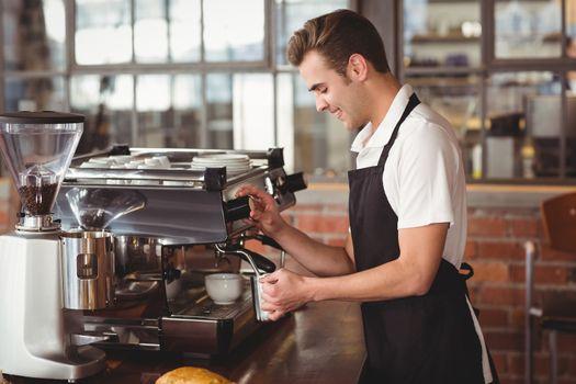 Smiling barista steaming milk at coffee machine