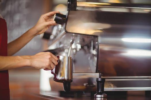 Barista steaming milk at the coffee machine