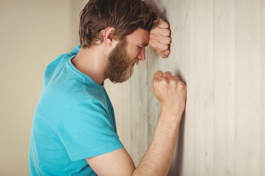Troubled hipster leaning against wall