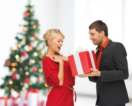 winter, holidays, christmas, celebration and people concept - smiling man and woman with present over living room with christmas tree background