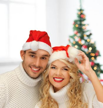 winter, holidays, celebration and people concept - smiling couple in sweaters and santa helper hats over living room with christmas tree background