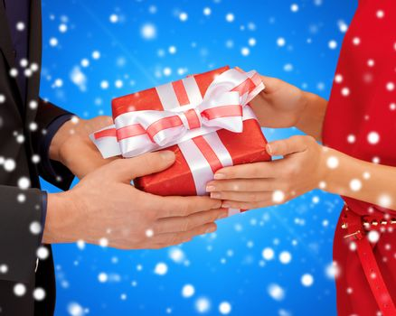 christmas, holidays, celebration and people concept - close up of man and woman with present over blue over blue snowy background