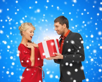 christmas, holidays, celebration and people concept - smiling man and woman with present over blue over blue snowy background