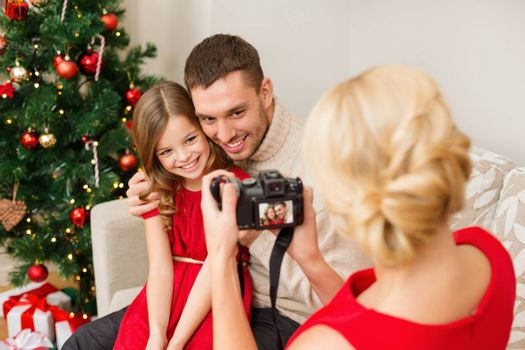 family, christmas, x-mas, happiness and people concept - mother taking picture of smiling father and daughter
