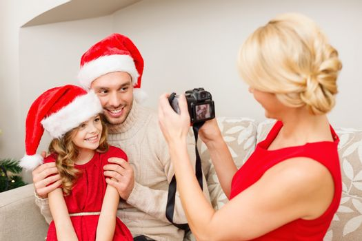 family, christmas, x-mas, happiness and people concept - mother taking picture of smiling father and daughter in santa helper hats