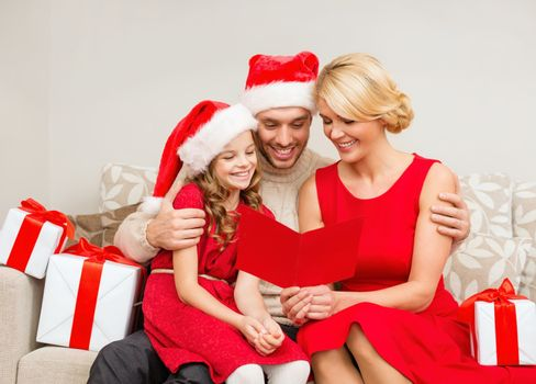 family, christmas, x-mas, happiness and people concept - smiling family in santa helper hats with many gift boxes reading postcard