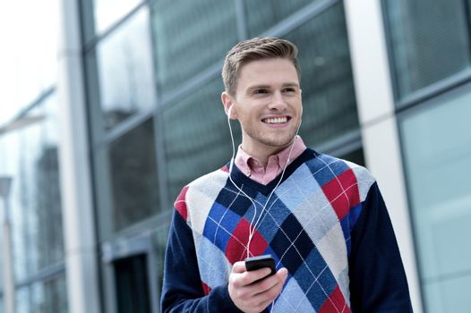 Casual man listening music on mobile phone