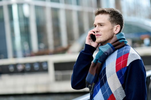Sideways of male listening on mobile at outdoor