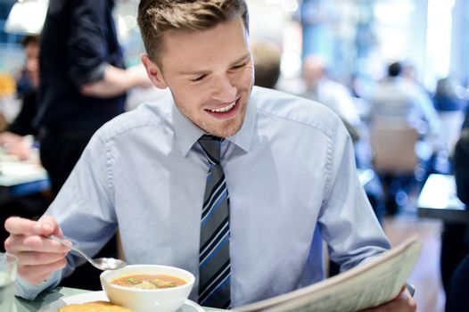 Happy executive reading a journal in cafe