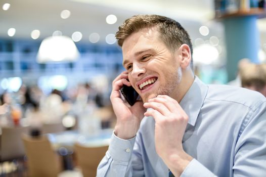 Young male executive talking on mobile in a cafe