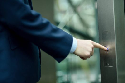 Close up of businessman finger pushing elevator button