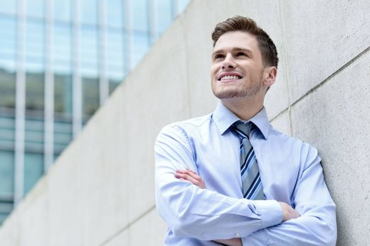Image of a corporate executive standing against wall