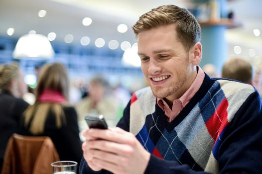Young man smiling as he reads message on his phone