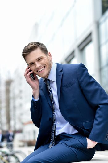 Image of a cheerful businessman talking on his cell phone