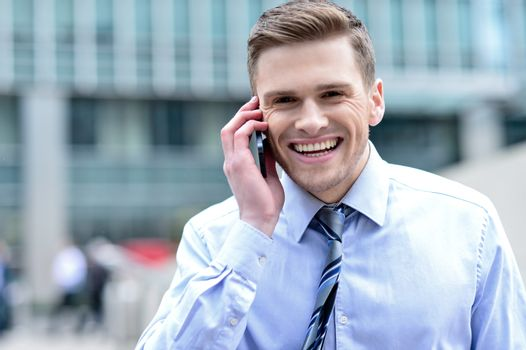 Cheerful male executive talking on his mobile