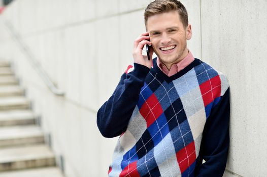 Casual man talking on cell phone, leaning on wall.