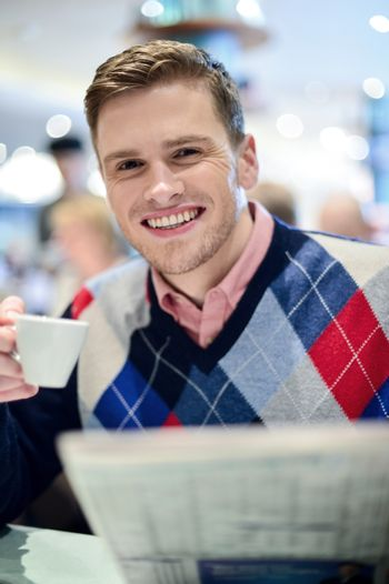 Young man posing at cafe with coffee cup
