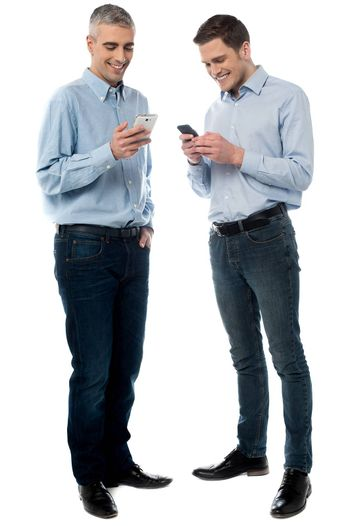 Casual men operating their new mobile phone