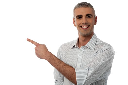 Image of a happy young man pointing to copy space