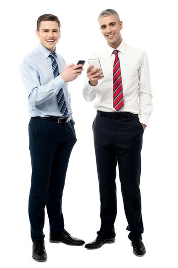 Happy male executives posing with cell phone